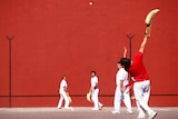 A group of men. Some stand in front of a red wall with the curved basket gloves used in pelota. One man is throwing a ball.