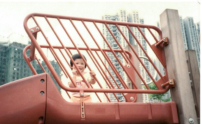 A little girl smiles from behind red railings at a playground with high rise in the background.