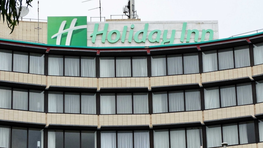 The exterior of a Holiday Inn hotel, with curtains drawn across windows and a green sign.