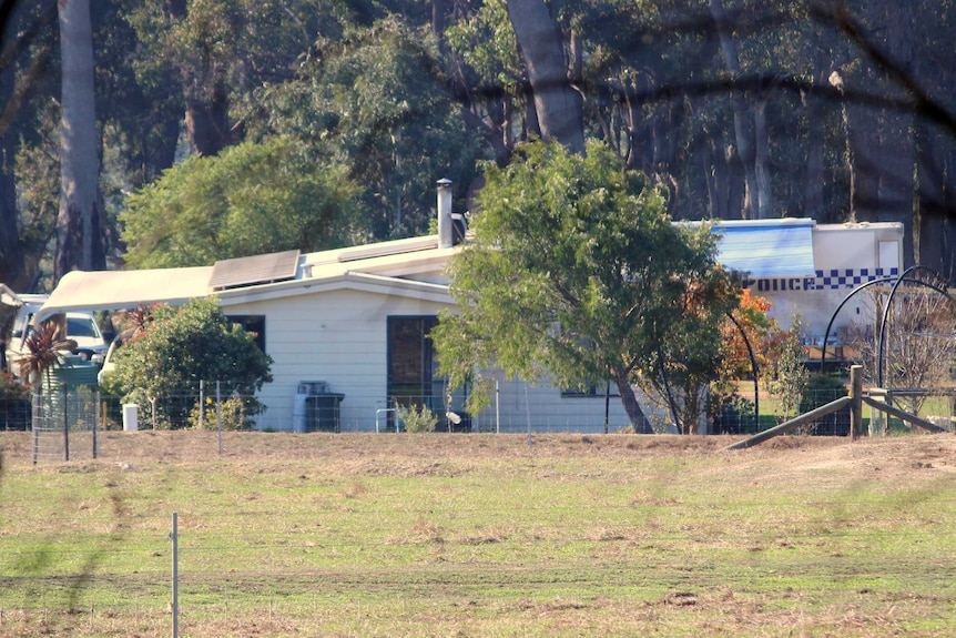 A shack-like home on a rural bush property with a police vehicle behind.
