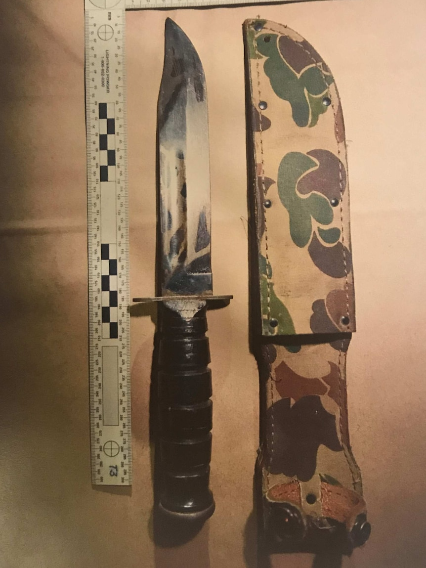 A hunting knife placed on a table next to a knife case