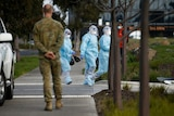 Health workers in full personal protective equipment walk into the Epping Gardens aged care home.