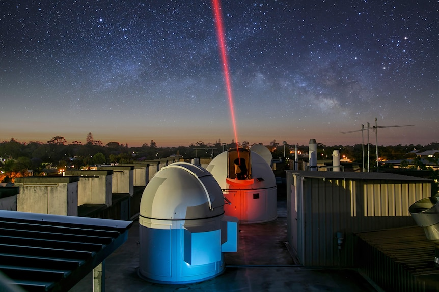 Telescope shooting a red laser into the sky