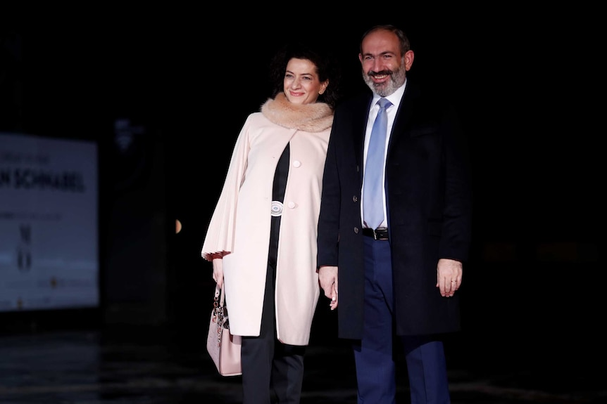 A bearded man with blue tie smiles as stands with a woman in a beige coat with fur collar.