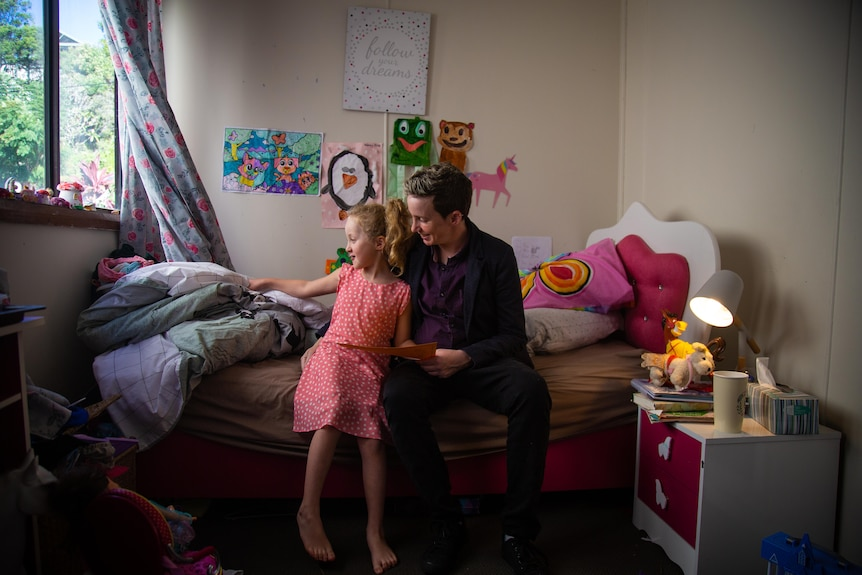 Mother and young daughter sitting together in child's bedroom.