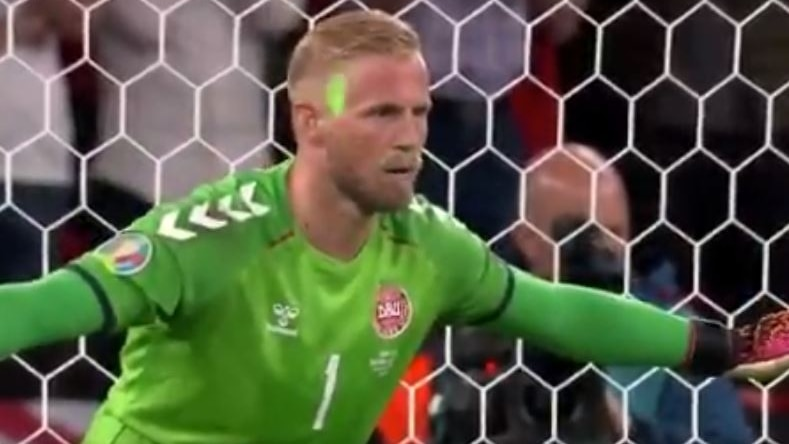 Kasper Schmeichel looks focussed despite the green light flashing on his face