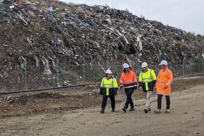 Four EPA staff members in high-vis jackets walk near a waste dump pile on a grey day.