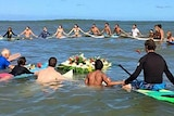 Surfers sit on their boards off the coast of Mexico and link hands during a paddle-out ceremony.