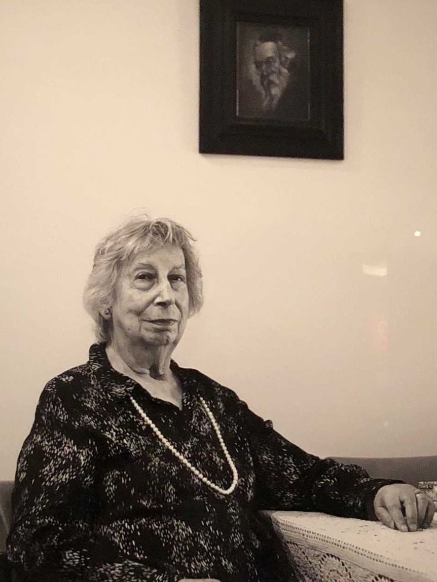 A picture of an elderly woman sitting at her dining room table, hangs in a frame at the Australian War Memorial.