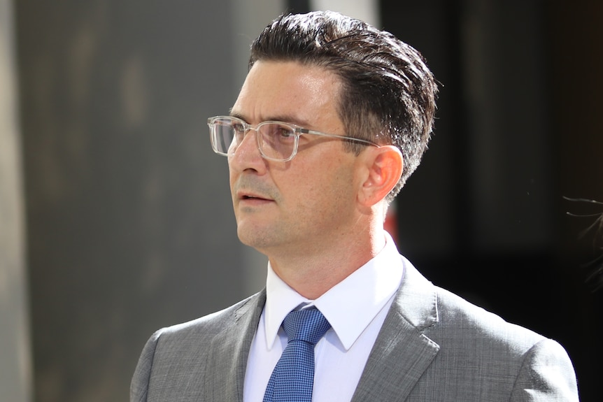 A head and shoulders shot of a man with dark hair wearing spectacles, a grey suit and a white shirt with a blue tie.