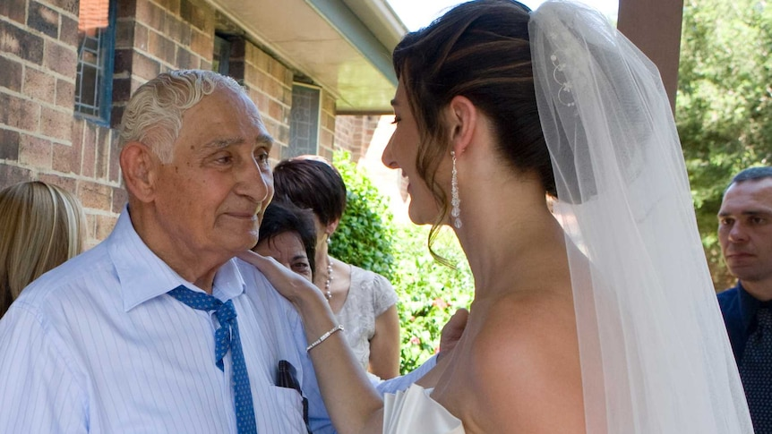 A bride smiles as she puts her hand on her grandfather's shoulder. He looks proud