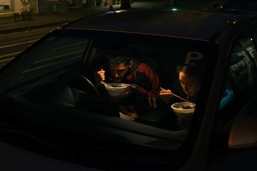 A young man and woman sit in the front seats of a car eating takeaway.
