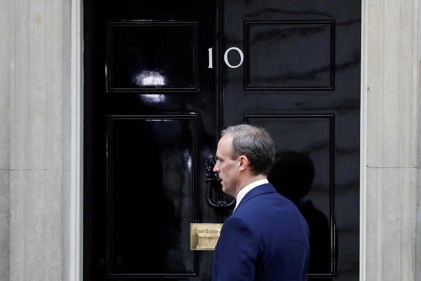 A man in a blue suit stands in front of a black door with the number 10 on it.