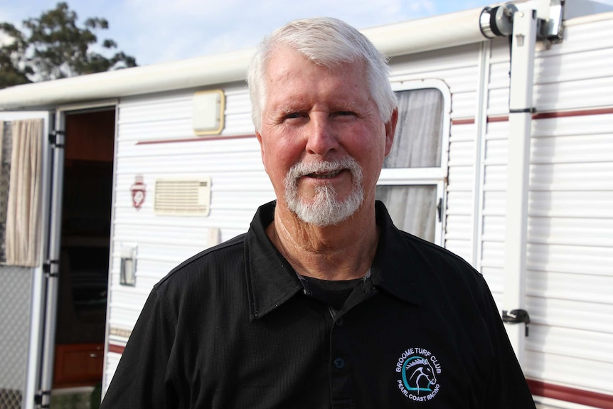 A head and shoulders shot of grey nomad Ian Baird standing in front of his caravan posing for a photo smiling.