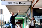 Michael Waite smiles standing under a hanging sign reading 'Naracoorte Community 'The News'.