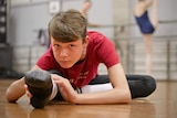 Ballet student Presley Tanner stretches his leg while seated on the ground