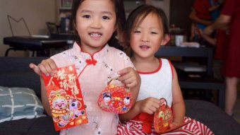 Two young girls hold red packets of money at Lunar New Year