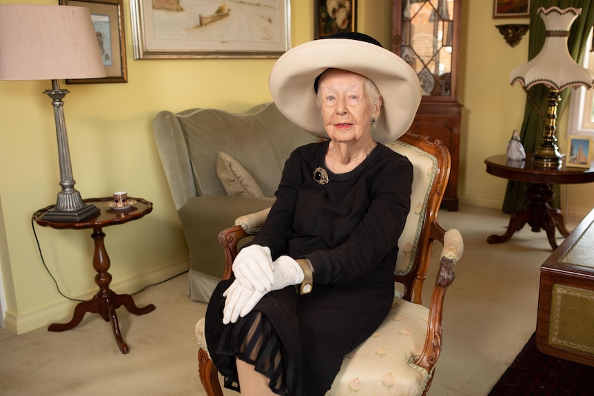 A woman in fine traditional clothing, including a wide-brim hat and gloves, poses on a chair for a photo.