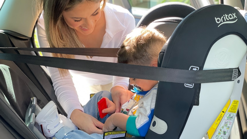 A woman buckles a seat belt in car seat with son inside.