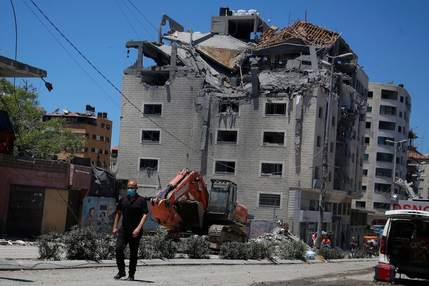 A man walks in front of a building that has suffered damage