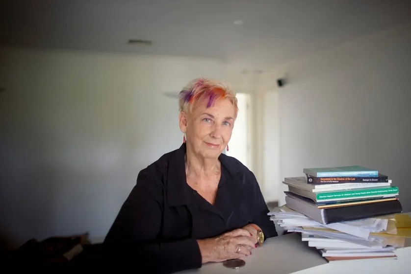 A photo of Thea Brown sitting at a desk next to a stack of books