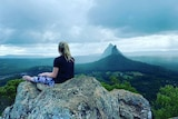 The back of a girl, sitting on the summit, looking out over the Glass House Mountains.