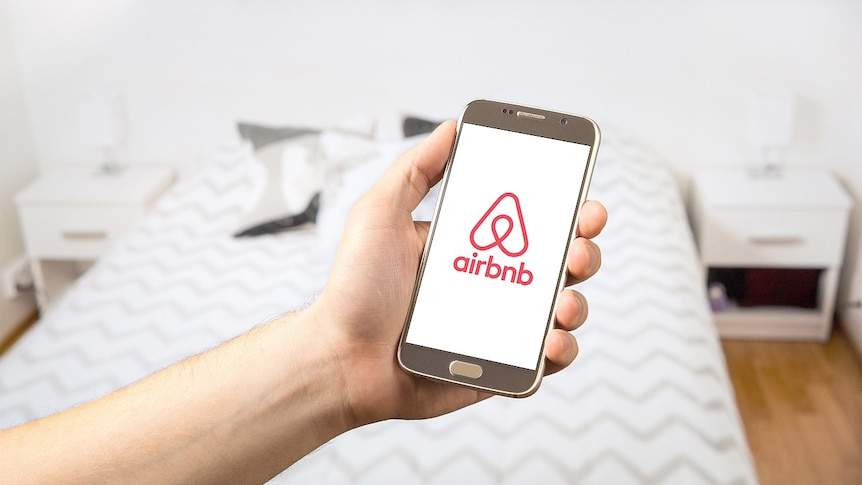 Airbnb app in a hand.