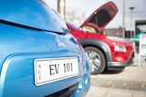 A close up of a licence plate on an electric vehicle reads:EV 101.