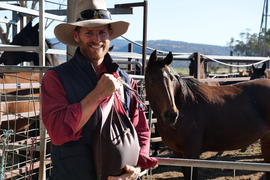 Gavin Heywood stands in front of a brown horse, holding a bag of horse blood.
