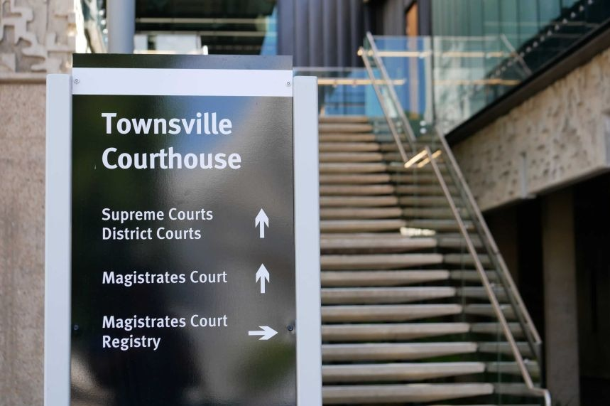 Black Townsville court house sign in front of set of stairs outside of the court house