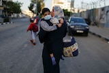 A woman in a headscarf walks holding a little boy in a face mask