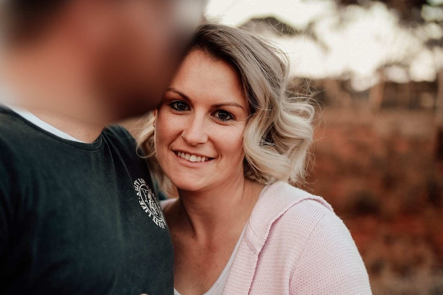 A blonde woman stares at the camera, with a red dirt background.