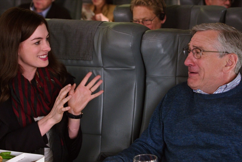 A young woman with brown hair gesticulates as she converses with an older bespectacled man seated next to her on airplane.