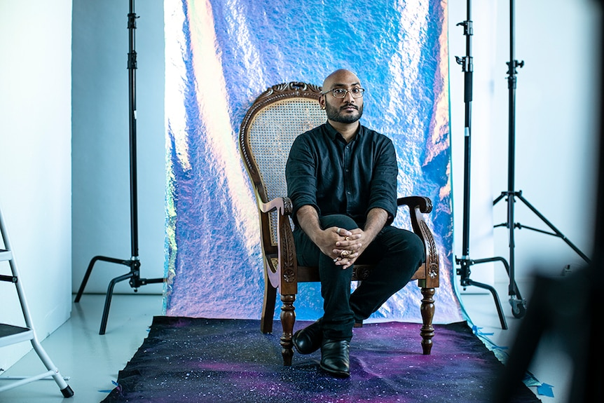 Fashion designer Lokesh Kashyap sitting with purple backdrop, at a shoot.