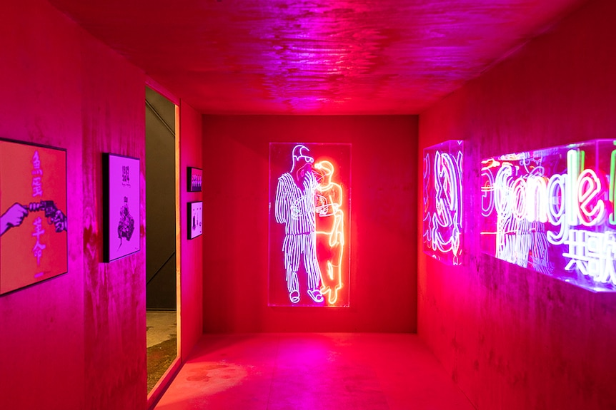 A neon light sculpture of two figures embracing illuminates a small gallery space with suspended artworks.
