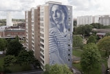 Very tall mural of a young woman on apartment block.
