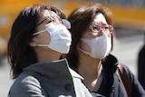 Two women in heavy coats wear face masks while walking outside.
