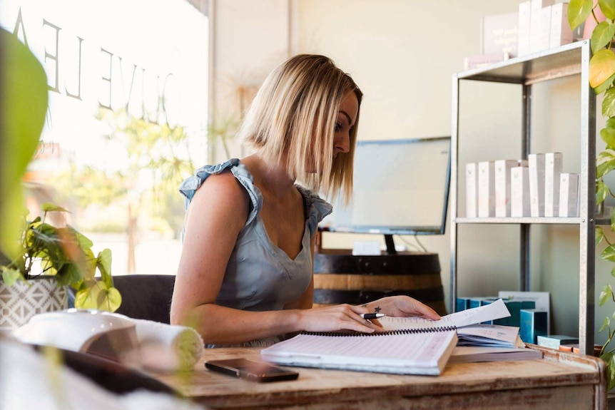 A woman with blonde haair and a blue top sits at a desk doing paperwork.