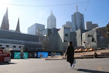 A man in a facemask walks past Melbourne's Federation Square, which is empty