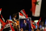 A small child and a picture of Bashar al-Assad held above a crowd of people celebrating.