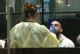 A woman hearing protective clothing puts a gloved hand up to the mouth of a man with a bald head