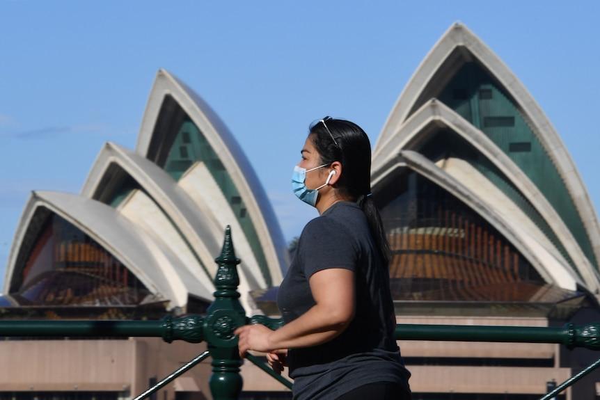 A woman walking past the Opera House.