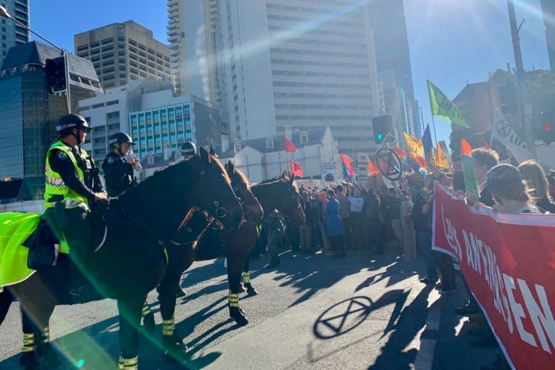Mounted police face hundreds of protesters holding signs on a street in Brisbane CBD.