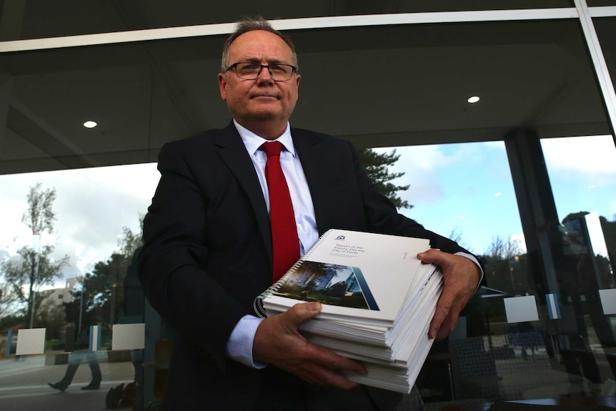 David Templeman holding the massive City of Perth report.