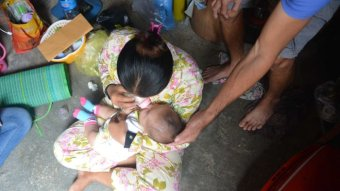 Father cradles baby's head as mother sits cross-legged in pjs and gives baby a bottle