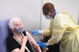 An older woman wearing a floral mask sits in a chair as a healthcare worker in PPE gives her a needle