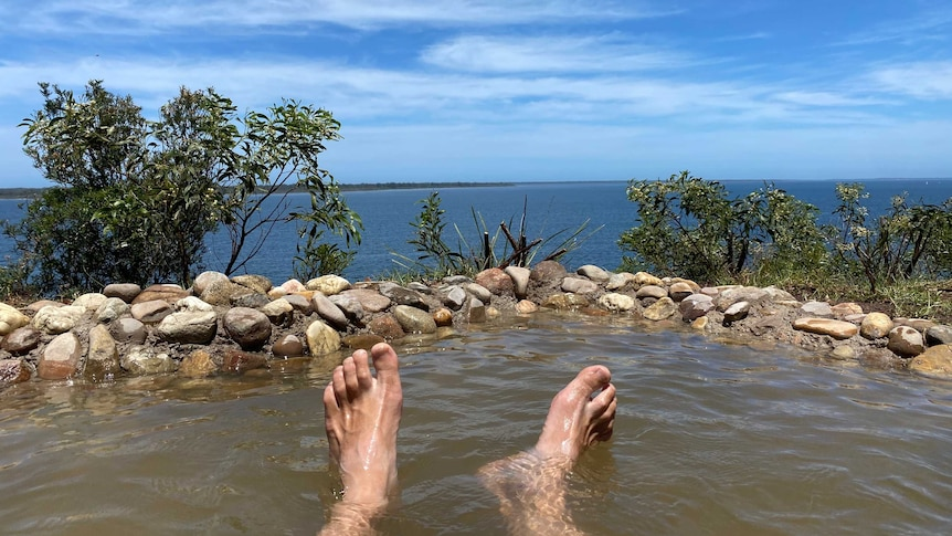 A man's feet in a hot springs pool that overlooks the ocean