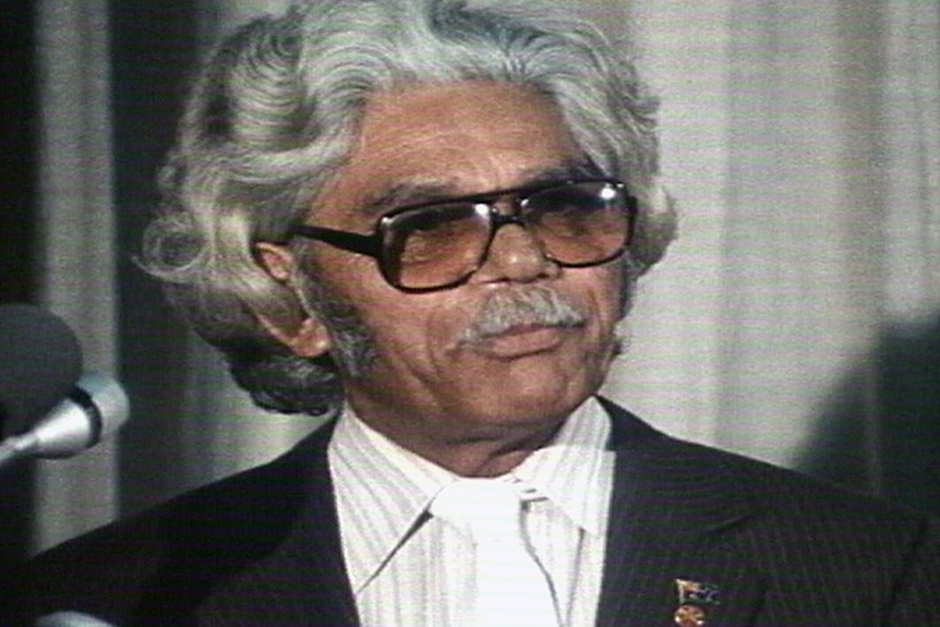 A head and shoulder shot of Neville Bonner wearing glasses and a pin-striped suit.