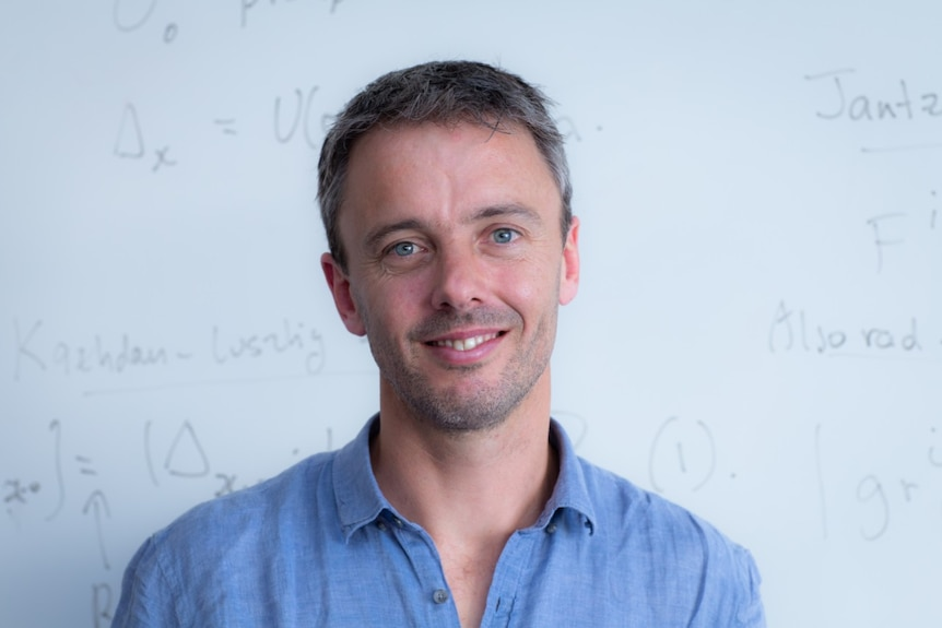 Australian mathematician Geordie Williamson in front of a white board.