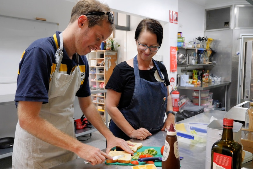 Jason buttering a slice of bread, Amanda watching on smiling, both standing in a kitchen.